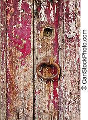Old grungy wooden door with peeling paint and door-handle -...