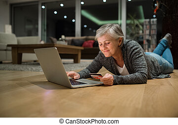 Senior woman with laptop lying on the floor shopping online...