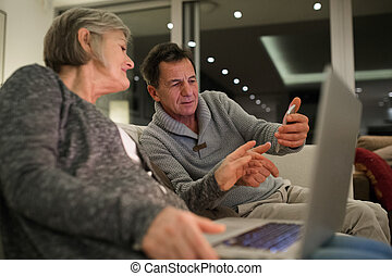Senior couple with laptop and smartphone sitting on couch -...