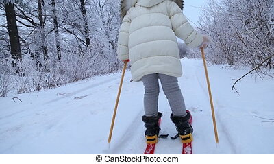 child skiing in the winter forest - Little girl skiing in...