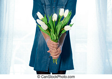 Girl is holding a bouquet of tulips