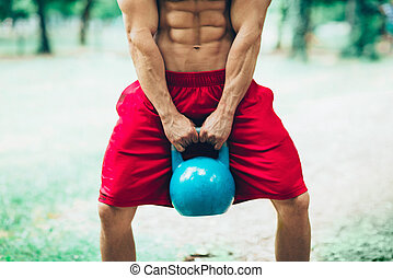 Male with kettle bell exercising outdoors