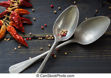 Two old tin spoons with red hot chili cayenne peppers dried,...