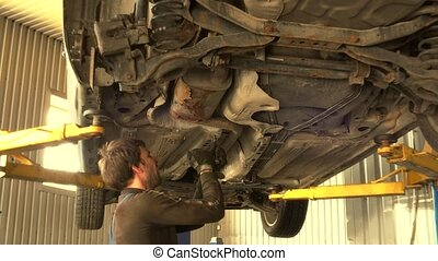 male mechanic unscrew car bottom protection bolts. man...