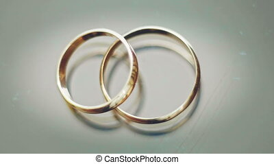 wedding rings lie on a grey background, glare from light 4k,...