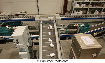 Medications move along a conveyor belt in the warehouse of...