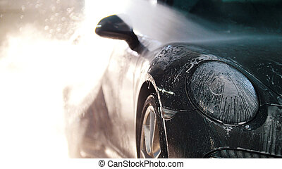 Worker in auto service is washing a luxury car by water...