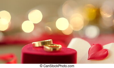 Gold wedding rings with bokeh lights on the background