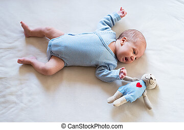 Cute newborn baby boy with teddy bear lying on bed - Cute...