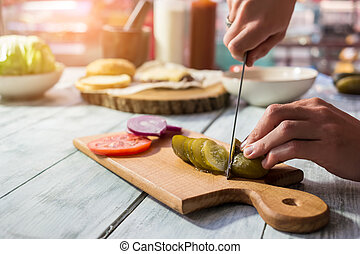Knife cutting pickled cucumber. Sliced vegetables on wooden...