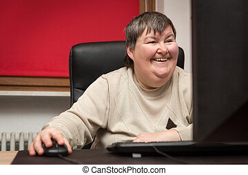 mentally disabled woman sitting at the computer, Education...