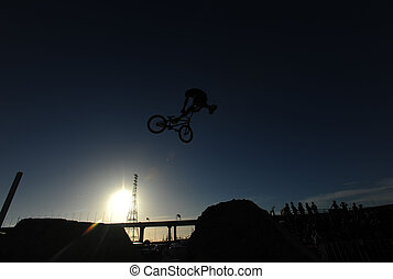 Dirt Bike Jump - A BMX rider is sillouetted against the blue...