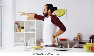 man eating breakfast and dancing at home