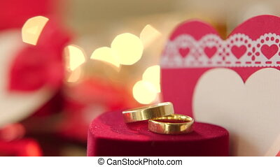 Gold wedding rings with bokeh lights and valentine on the...