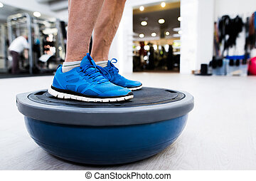 Unrecognizable senior man in gym standing on bosu balance...