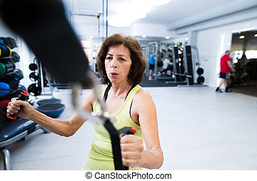 Senior woman in gym working out with weights.