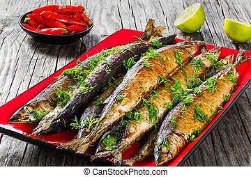 Baked saury on a red rectangular dish , close-up top view
