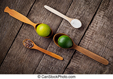 Lime on spoons with salt and sugar spoon on the kitchen...