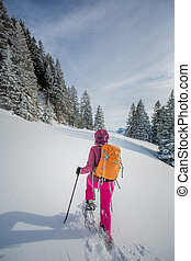 Pretty, young woman snowshoeing in high mountains, enjoying