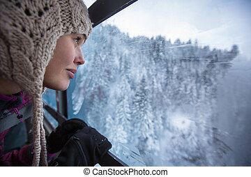 Pretty, young woman admiring splendid winter scenery from a...