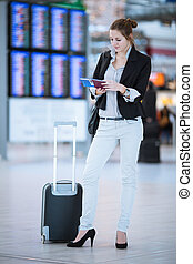 Pretty young female passenger at the airport (shallow DOF;...