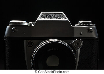 Old film camera - low key image - Modern DSLR camera with a...