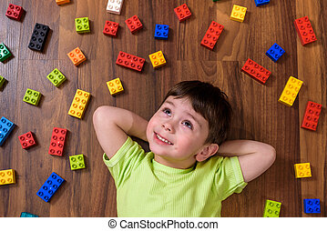 Little caucasian child playing with lots of colorful plastic...