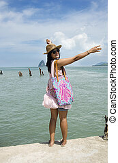 Asian thai woman traveling and posing at harbour with sea...