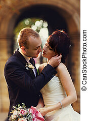 Groom leans to a bride and touches her face before a kiss