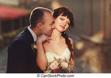 Groom touches bride's delicate neck with his nose while they...