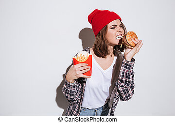Woman holding fries and burger - Picture of hungry woman...