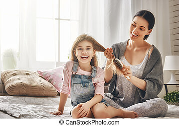 Happy loving family. Mother is combing her daughter's hair...