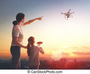 Kid and mom playing with drone - Little girl and her mother...