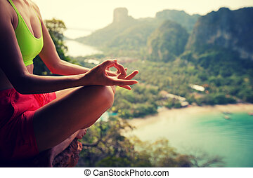 young healthy woman practice yoga on mountain peak cliff