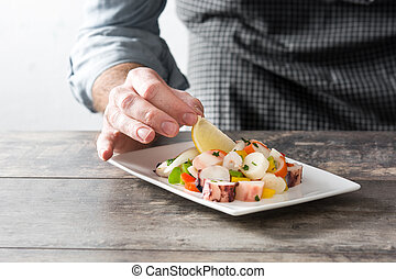 Chef preparing seafood ceviche on wooden table