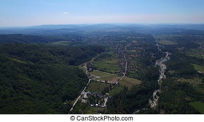 Aerial view of Polovragi commune and green hills, Romania