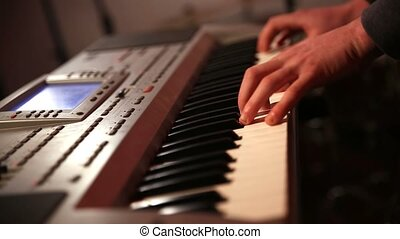 Man playing synthesizer keyboard - Middle section of man...