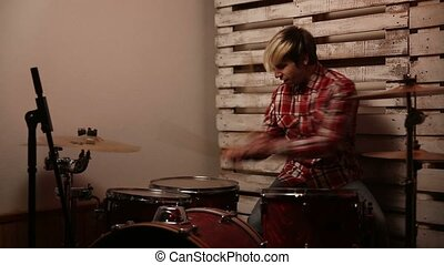 Expressive drummer playing on drums in club - Young excited...