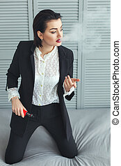 Business woman smokes. - Woman in a business suit smokes...