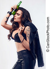 Young sexy girl with long hair in leather jacket with beer -...