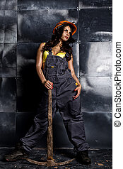 Sexy female miner worker with pickaxe, in coveralls.