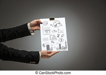 Male hands holding business plan on blank on dark background...
