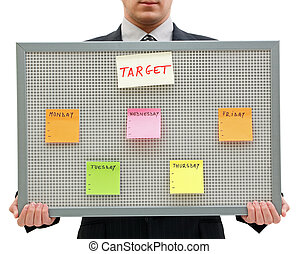 Weekly target - Businessman holding a reminder board with...