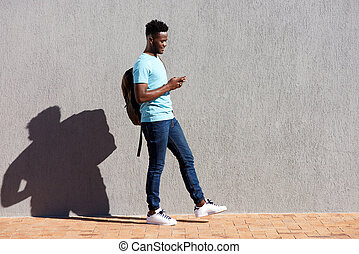 College student walking with bag and mobile phone - Full...
