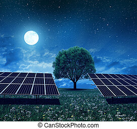 Solar power station on the meadow in night.