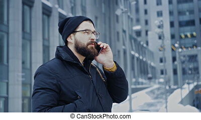 Man hipster talking on phone saying goodbye in front of...