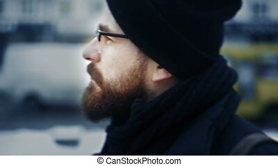Close-up of caucasian man in hat cap and glasses turning head on winter street
