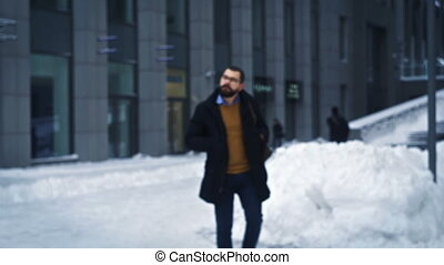 Man walking in city, making photo on business street, tourist in winter city