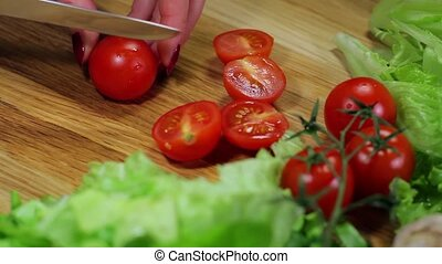 cutting cherry tomatoes - preparation of salad with fresh...