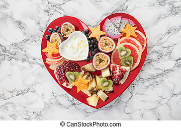 Fresh exotic fruits on red heart shaped plate